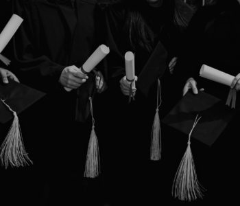 four-grad-students-caps-and-diplomas